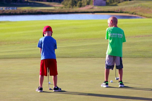Two young boys putting on the Old Hawthorne golf course