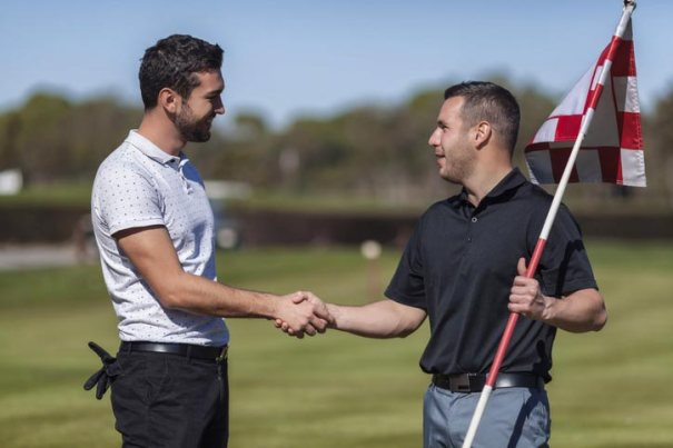 Men on golf course green shaking hands