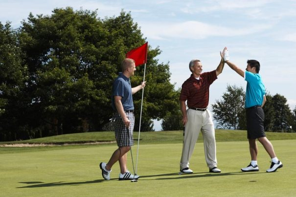 Three male golfers on green, one holds the flag, other two high-five